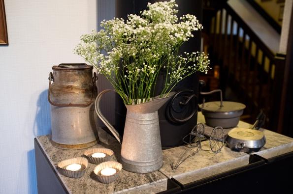 Mjölkkanna-och-blommor-på-kamin